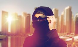Muslim woman in hijab and sunglasses in dubai city. Accessory, fashion and people concept - muslim woman in hijab and sunglasses over dubai city street Royalty Free Stock Photos