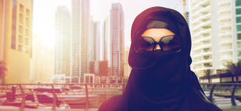 Muslim woman in hijab and sunglasses at dubai city. Accessory, fashion and people concept - muslim woman in hijab and sunglasses over dubai city street Stock Photography