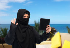 Muslim woman in hijab with tablet pc having chat Stock Images