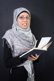 Muslim woman holding a book. Young muslim woman holding a book Stock Images