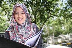 Muslim woman holding a file. Cheerful uslim mbusiness woman holding a file Stock Photo