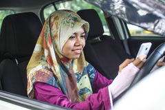 Muslim woman holding handphone while driving Stock Photos