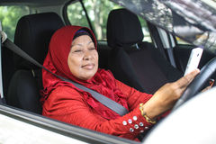 Muslim woman holding handphone while driving Stock Photo