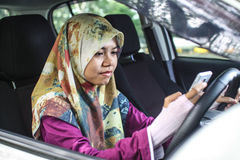 Muslim woman holding handphone while driving Royalty Free Stock Photo