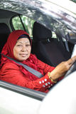 Muslim woman holding handphone while driving Stock Images