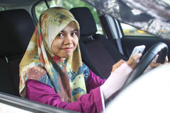Muslim woman holding handphone while driving Royalty Free Stock Image