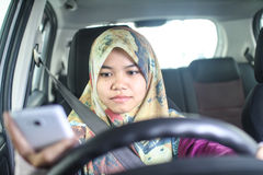 Muslim woman holding handphone while driving Stock Image
