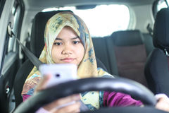 Muslim woman holding handphone while driving Royalty Free Stock Photography