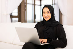 Muslim woman laptop. Modern muslim woman using laptop in living room at home royalty free stock photo