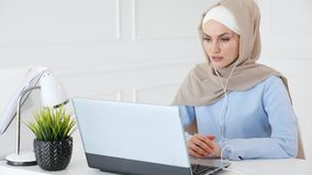 Muslim woman is learning english in earphones online using computer. Portrait of young muslim woman in hijab and traditional clothes is learning english in stock video footage
