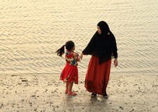 Muslim woman with little girl walking on beach. Muslim woman with little girl walking on sandy beach during sunset (Sorong, Papua Barat, Indonesia Stock Photo
