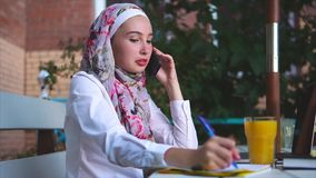 A Muslim woman makes an important call on mobile phone makes notes in a notebook stock video footage