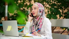 Muslim woman making business phone call. Young Muslim woman working in relaxing atmosphere of outdoor cafe. She talking on business and using laptop stock video footage
