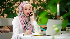 Muslim woman making business phone call stock footage
