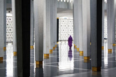 Muslim woman at Masjid Negara mosque in KL. A muslim woman totally covered in purple wanders around in the Masjid Negara mosque in Kuala Lumpur, Malaysia Stock Images