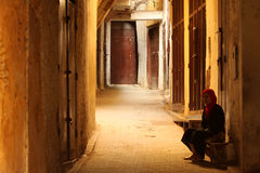 Muslim woman in the medina. Muslim woman sitting on the empty street in the early morning, medina, Fez, Morocco Stock Photos