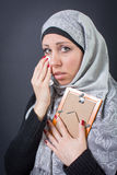 Muslim woman moaning over a photograph royalty free stock image