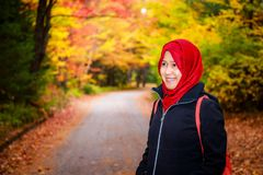 Muslim woman in North America. During autumn with colorful maple leaf as background royalty free stock photography