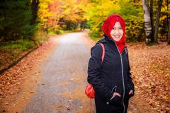 Muslim woman in North America. During autumn with colorful maple leaf as background royalty free stock photos