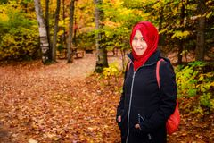 Muslim woman in North America. During autumn with colorful maple leaf as background royalty free stock image