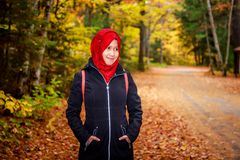 Muslim woman in North America. During autumn with colorful maple leaf as background stock images