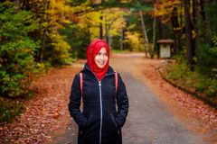 Muslim woman in North America. During autumn with colorful maple leaf as background royalty free stock images