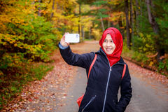 Muslim woman in North America. During autumn with colorful maple leaf as background stock image