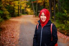 Muslim woman in North America. During autumn with colorful maple leaf as background stock photo