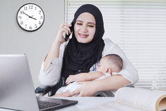 Muslim Woman Nursing her Baby while Working Stock Images