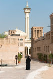 Muslim woman in old arabic district with mosque. Woman in traditional muslim black dress in old arabic city district with mosque minaret on background Royalty Free Stock Photo