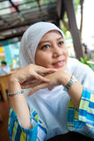 Muslim woman at an outdoor cafe. Muslim woman staring out while enjoying a day out Royalty Free Stock Photos