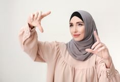 Muslim woman pointing on virtual screen, copy space. Innovation and future technologies, virtual screen gesture. Islamic woman in hijab showing frame with hands Royalty Free Stock Photography
