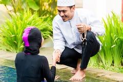 Muslim woman in pool greeting her husband. Muslim women or girl in swimming pool in tropical garden wearing Burkini halal swimwear greeting her husband Royalty Free Stock Images