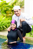 Muslim woman in pool greeting her husband Royalty Free Stock Photos