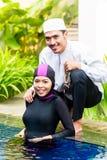 Muslim woman in pool greeting her husband. Muslim women or girl in swimming pool in tropical garden wearing Burkini halal swimwear greeting her husband Royalty Free Stock Photos