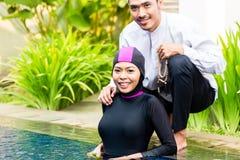Muslim woman in pool greeting her husband. Muslim women or girl in swimming pool in tropical garden wearing Burkini halal swimwear greeting her husband Royalty Free Stock Image