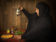 Muslim woman pouring tea stock images
