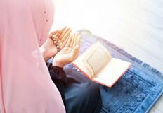 Muslim woman pray with beads and read quran