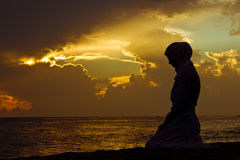 Muslim woman praying. Young muslim woman praying at sunset Stock Images
