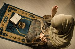 Muslim woman praying for Allah muslim god at room near window. Hands of muslim woman on the carpet praying in traditional wearing. Clothes, Woman in Hijab stock images