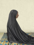 Muslim woman praying at home, sitting on a straw mat Stock Images