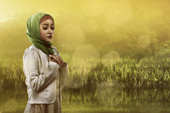 Muslim woman praying. Image of asian muslim woman praying on the field Stock Images