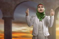 Muslim woman praying. Image of muslim woman praying over mosque background Royalty Free Stock Image