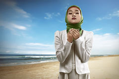 Muslim woman praying. Image of muslim woman praying over mosque background Stock Image