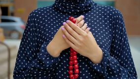 Muslim woman praying with islamic beads in hand, religious meditation, worship. Red beads in the hands of Muslim women stock video footage