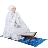 Muslim woman praying with Koran. Portrait of muslim woman looks religious, wearing islamic clothes and praying on mat with a Koran Stock Images