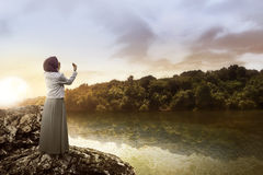 Muslim woman praying at the lake. Young muslim woman praying standing on the rock at the lake Stock Image