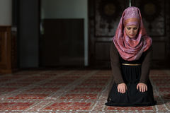 Muslim Woman Is Praying In The Mosque. Young Muslim Woman Praying In Mosque Stock Photo