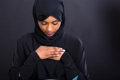 Muslim woman praying. Mysterious muslim woman praying on black background Stock Image