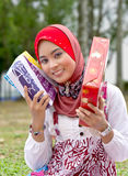 Muslim woman with presents. Happy young muslim woman in traditional hijab with wrapped presents or gifts Stock Photo